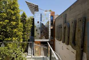 The exterior of David Baker's Zero Cottage is clad in metal shingles. Some were replaced with planters that contain succulents.