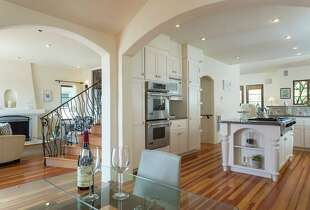 The kitchen includes white cabinetry and stainless steel appliances.