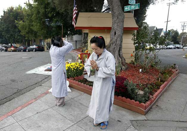 Vina Vo (left) and Kieu Do pray at sunrise near a Buddhist shrine at 11th Avenue and East 19th Street in Oakland. Photo: Paul Chinn, The Chronicle