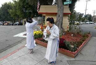 Vina Vo (left) and Kieu Do pray at sunrise in front of a Buddhist altar erected at 11th Avenue and East 19th Street in Oakland, Calif. on Saturday, Sept. 13, 2014.