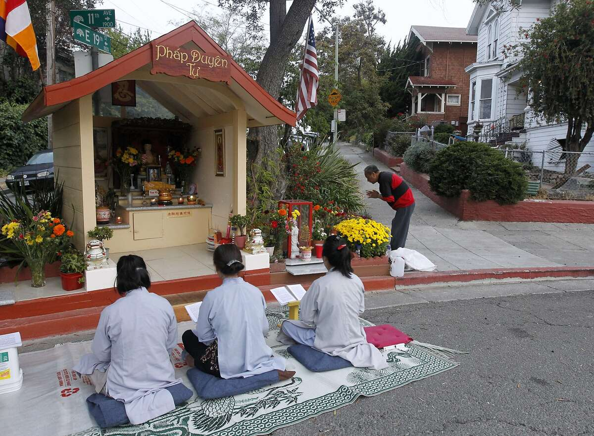 Vina Vo (left), Lien Huynh and Kieu Do gather for a daily prayer session at sunrise in front of a Buddhist altar erected at 11th Avenue and East 19th Street in Oakland, Calif. on Saturday, Sept. 13, 2014.