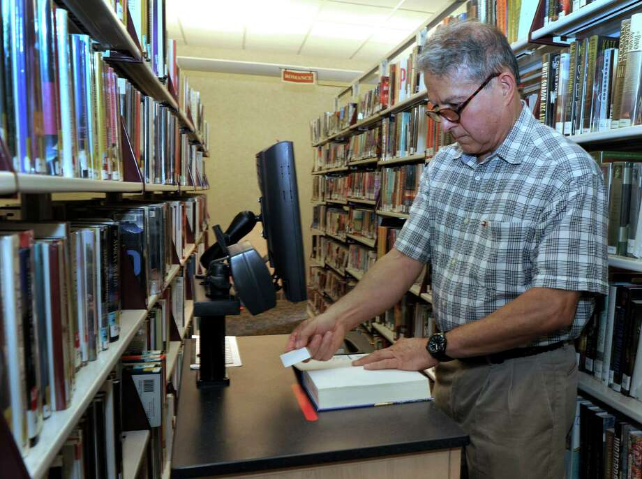 Ramiro Estrada, 65, of Bethel, electronically tags books at the Danbury Public Library on Monday, Sept. 15, 2014. Photo: Carol Kaliff / The News-Times