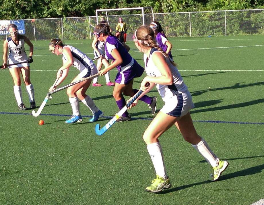 Staples senior Meg Fay controls the ball while Westhill's Jessica Souza chases her down while Elizabeth Bennewitz (left) looks on during a field hockey game on Monday. Staples won 4-2. Photo: Ryan Lacey/Staff Photo / Westport News Contributed