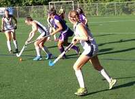 Staples senior Meg Fay controls the ball while Westhill's Jessica Souza chases her down while Elizabeth Bennewitz (left) looks on during a field hockey game on Monday. Staples won 4-2.