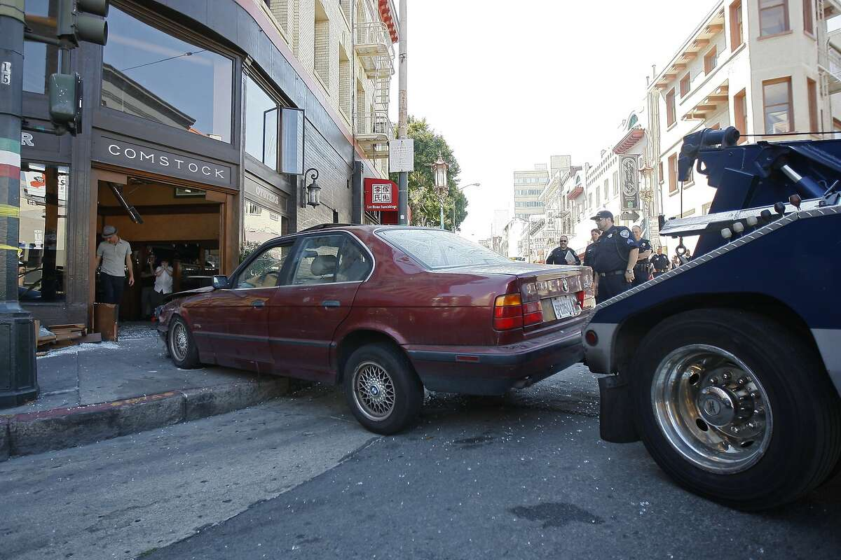 A BMW is towed out of Comstock Saloon on the corner of Columbus and Pacific Avenue in San Francisco, Calif. after the driver crashed through the front doors Monday, September 15, 2014.