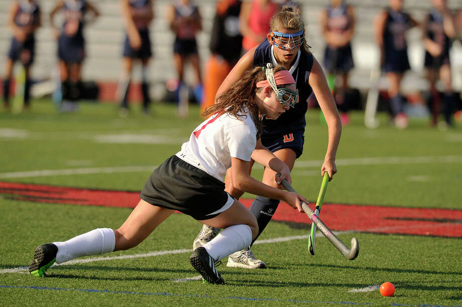 Greenwich's Erika Hvolbeck gets the pass off before falling to the ground while under pressure from Danbury's Natalia Prukalski during their field hockey game at Greenwich High School in Greenwich, Conn., on Monday, Sept. 15, 2014. Greenwich won, 1-0. Photo: Jason Rearick / Stamford Advocate