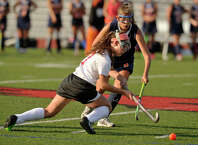 Greenwich's Erika Hvolbeck gets the pass off before falling to the ground while under pressure from Danbury's Natalia Prukalski during their field hockey game at Greenwich High School in Greenwich, Conn., on Monday, Sept. 15, 2014. Greenwich won, 1-0.