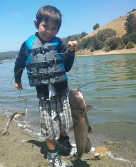 A young angler shows off a catfish from Lake Chabot. The 315-acre lake is stocked with catfish, trout, bass, crappie and bluegill.