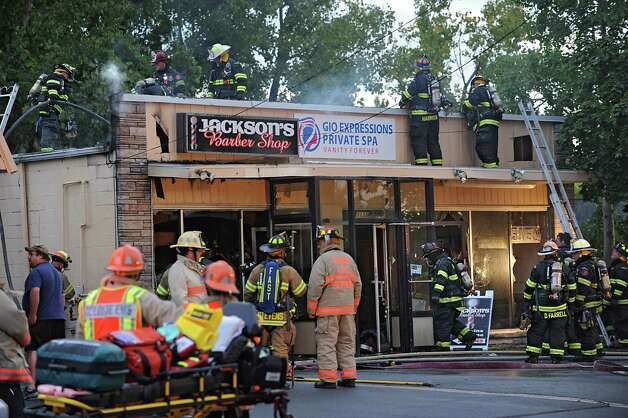 Firefighters attend a working fire at a building on Everett Rd. on Monday, Sept. 15, 2014 in Colonie, N.Y. The building contained the three businesses, Jackson's Barbershop, Gio Expressions Private Spa and Anthony's Pizza Palace. (Lori Van Buren / Times Union) Photo: Lori Van Buren