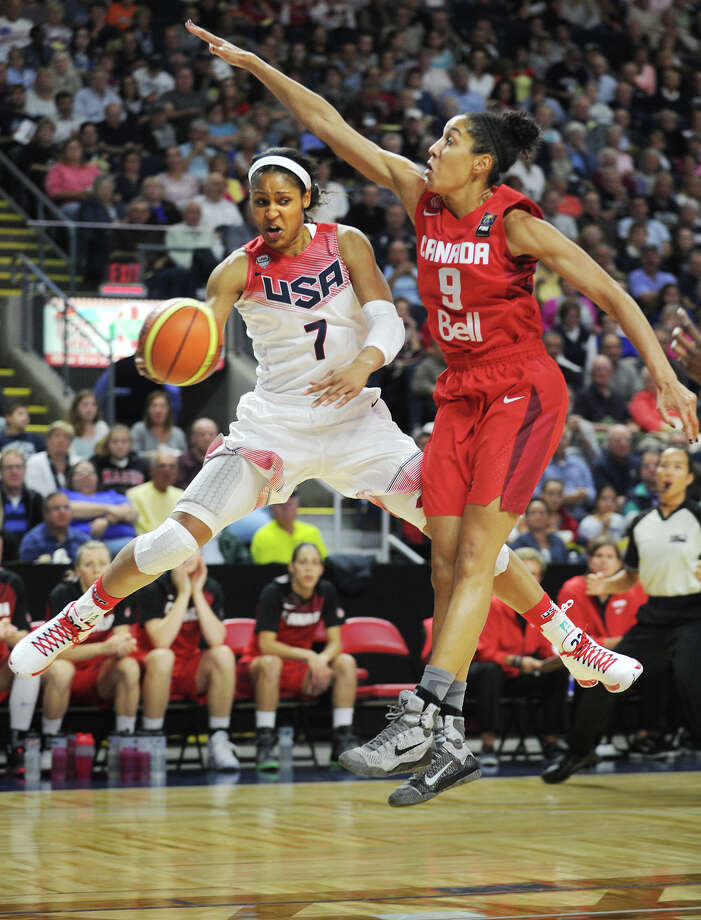 Former UCONN women's basketball and Team USA star Maya Moore passes around Team Canada's Miranda Ayim during a matchup of the two national teams at the Webster Bank Arena in Bridgeport, Conn. on Monday, September 15, 2014. Photo: Brian A. Pounds / Connecticut Post