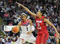 Former UCONN women's basketball and Team USA star Maya Moore passes around Team Canada's Miranda Ayim during a matchup of the two national teams at the Webster Bank Arena in Bridgeport, Conn. on Monday, September 15, 2014.