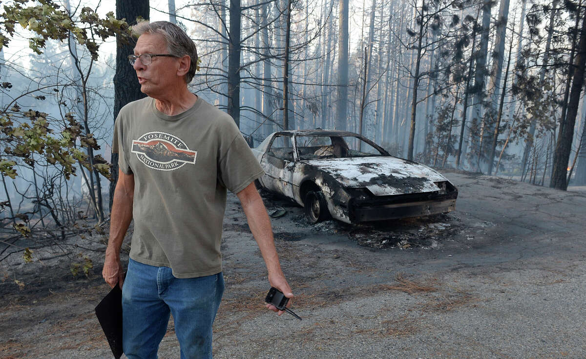 Jon Cunningham looks at the destruction near where his house burned in Oakhurst, Calif., Sunday, Sept. 14, 2014, as two raging wildfires in the state forced hundreds of people to evacuate their homes. The California Department of Forestry and Fire Protection said flames damaged or destroyed 21 structures. The Fresno Bee reports one neighborhood was hit especially hard, with several homes turned to ash and smoldering embers. (AP Photo/The Fresno Bee, Mark Crosse)
