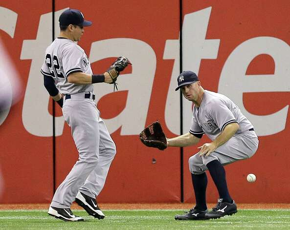 New York Yankees left fielder Brett Gardner, right, drops a fly ball by Tampa Bay Rays' James Loney after bumping into center fielder Jacoby Ellsbury, left, during the fourth inning of a baseball game Monday, Sept. 15, 2014, in St. Petersburg, Fla. Gardner was charged with an error on the play. (AP Photo/Chris O'Meara) ORG XMIT: SPD109 Photo: Chris O'Meara / AP