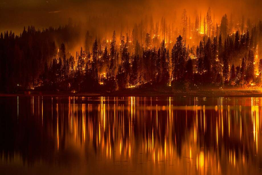 This Sunday, Sept. 14, 2014 photo shows fire as it approaches the shore of Bass Lake, Calif. Crews are attempting to get better access to two raging wildfires in California Monday that have forced hundreds to evacuate their homes. Photo: Darvin Atkeson, Associated Press