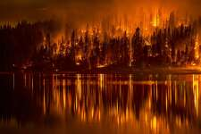 This Sunday, Sept. 14, 2014 photo shows fire as it approaches the shore of Bass Lake, Calif. Crews are attempting to get better access to two raging wildfires in California Monday that have forced hundreds to evacuate their homes. (AP Photo/YosemiteLandscapes.com. Darvin Atkeson )