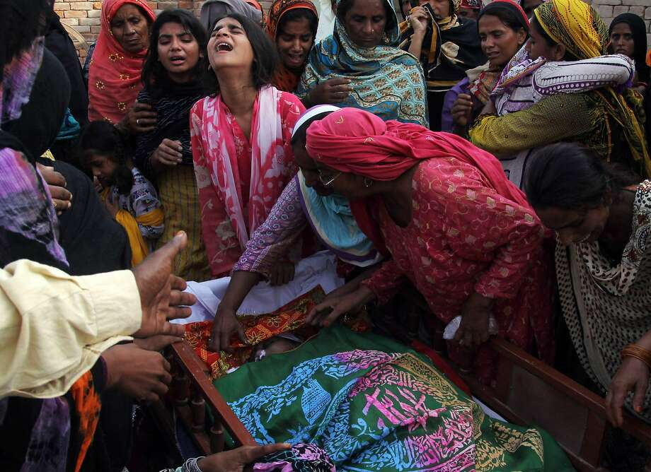TOPSHOTS Pakistani relatives mourn over the body of a resident who drowned when the boat he was travelling in capsized following flooding in Multan on September 15, 2014. At least 17 people including a bridegroom and two children drowned on September 14 when a rescue boat carrying a wedding party capsized in flood-hit central Pakistan, officials said. Floods and landslides from days of heavy monsoon rains have now claimed almost 500 lives in Pakistan and India. AFP PHOTO/ SS MIRZASS MIRZA/AFP/Getty Images Photo: Ss Mirza, AFP/Getty Images