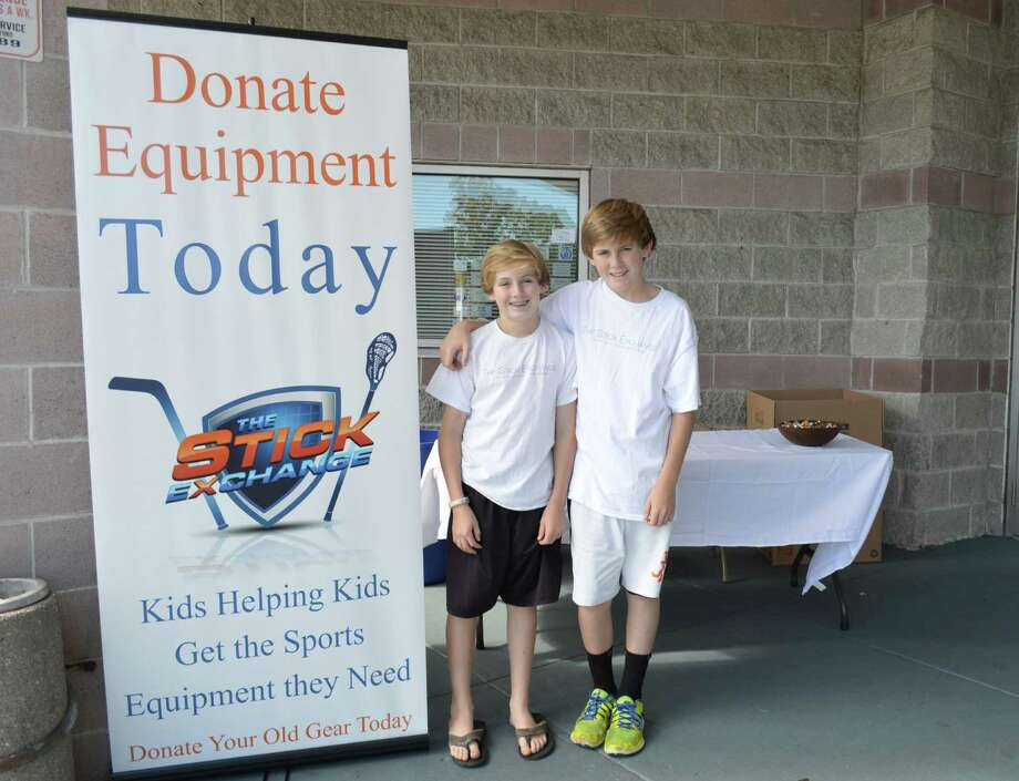 From left, Charlie and James Tait outside Stamford Twin Rinks, 1063 Hope St., Stamford, Conn., in September 2013. For the third consecutive year, the brothers and their family will be collecting new and used hockey equipment at Stamford Twin Rinks between 2 and 5 p.m. Saturday and Sunday, Sept. 20 and 21. Photo: Contributed Photo, Contributed / New Canaan News Contributed