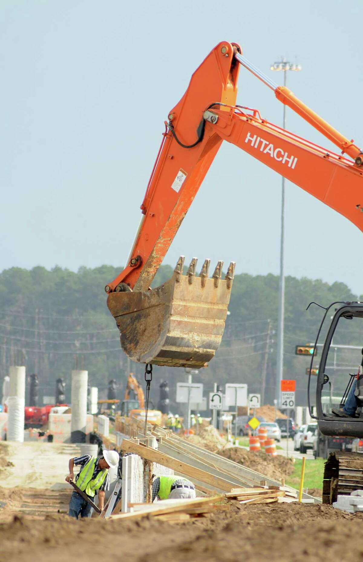 Workers install retaining walls along Texas 249.