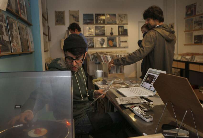Owner Chris Dixon (front) plays an album at the Explorist in San Francisco, Calif., as customers Mario Martinez and his 1 year old son Allen Martinez browse on Tuesday, September 2, 2014. Mario bought two fourty fives --the batman theme from the sixties and and a french mid seventies prog-rock song.