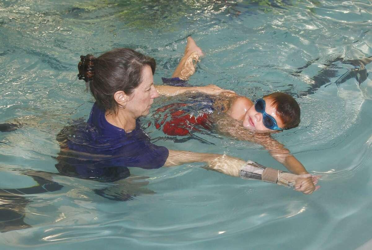 Swim instructor Sarah Hays teaches swimming stroke skills to Trevor Svoboda, 4, at the Texas Swim Academy in Katy.