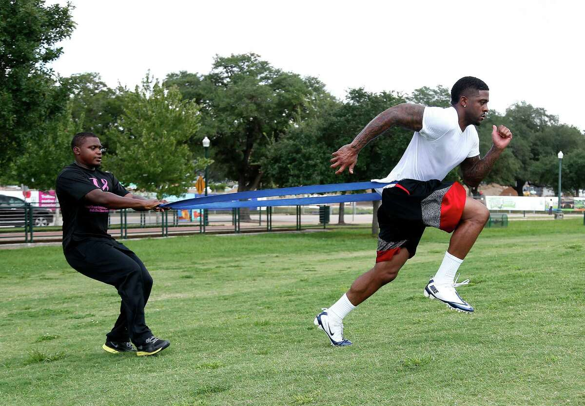 Performance Specialist Darelle Noel, works with Joe Anderson, at Hermann Park, Monday, Sept. 15, 2014, in Houston. Anderson was recently released from the Philadelphia Eagles and was working out with David Hunter, released by the Houston Texans.