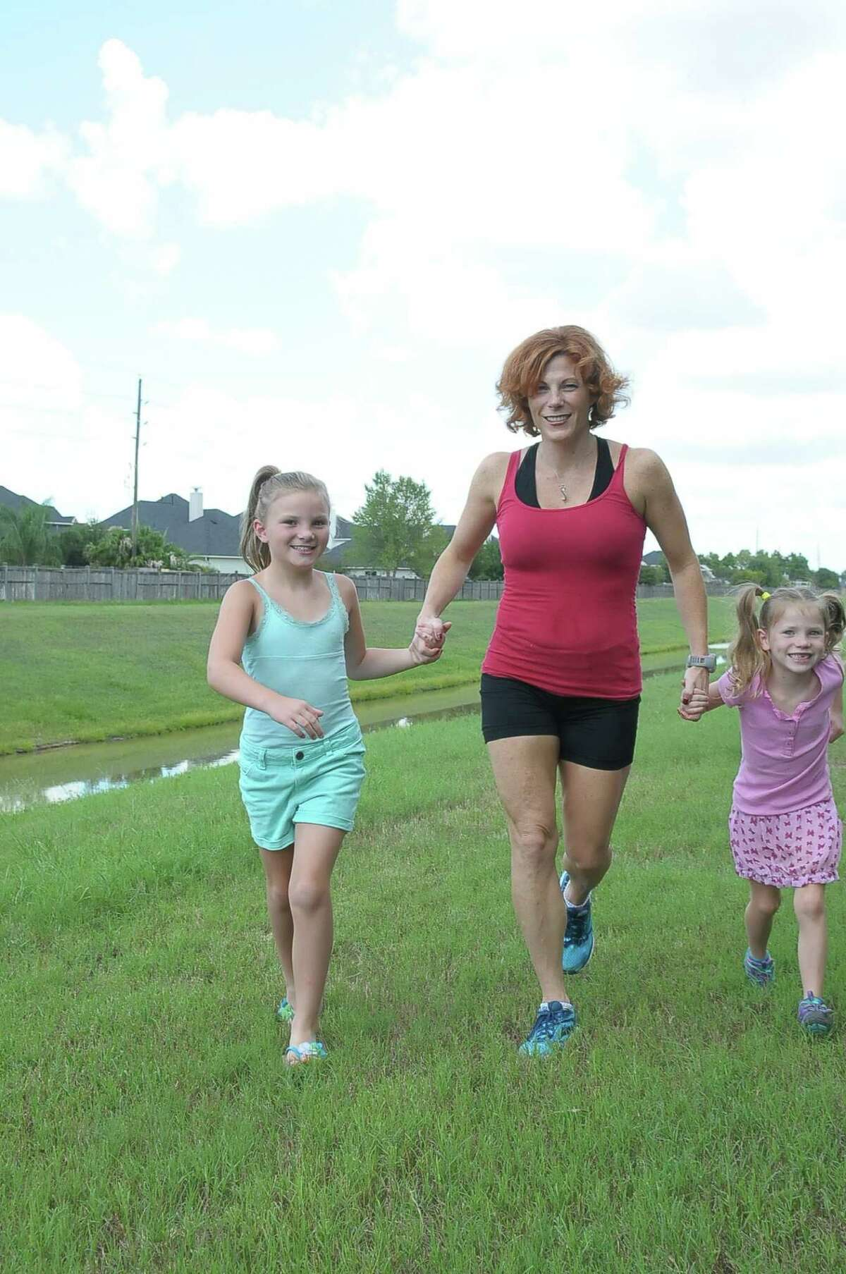 Kimberly Rensel runs with her daughters Sadie Rensel, 7½, and Savannah Rensel, 6, near their home in Katy. She is running to raise money to go on a mission to Africa. Kimberly Rensel runs with her daughters Sadie Rensel, 7½, and Savannah Rensel, 6, near their home in Katy. She is running to raise money to go on a mission to Africa.