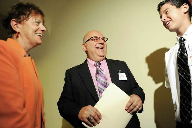 Gloversville High Latin teacher Charles Giglio, New York State Teacher of the Year, center, talks with Catalina Fortino, vice president of NYSUT, left, and Kyle Fonda, 15, one of Giglio's Latin students, on Tuesday, Sept. 16, 2014, at the State Education Building in Albany, N.Y. (Cindy Schultz / Times Union) Photo: Cindy Schultz / 10028644A