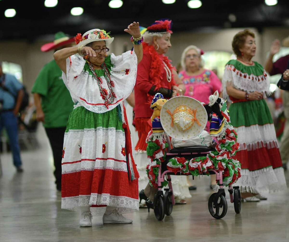 Margaret Arriaga, 80, dances by her gaily decorated walker during the Senior Kermes, celebrating Mexico's Independence Day holiday of Diez y Seis de Septiembre, at the Henry B. Gonzalez Convention Center on Tuesday, Sept. 16, 2014.