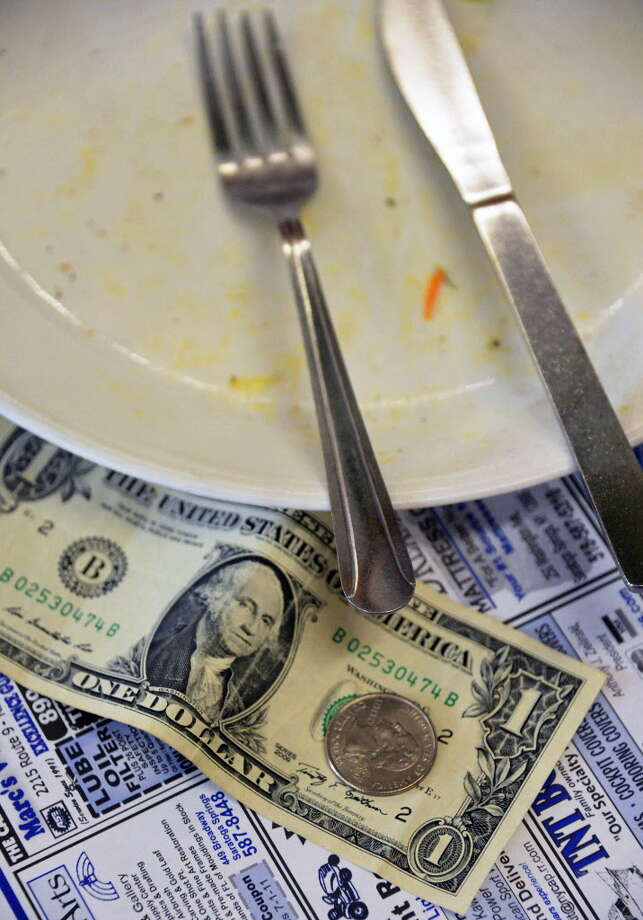 A tip left next to an empty breakfast plate at Compton's Restaurant in Saratoga Springs Thursday Sept. 6, 2012.  (John Carl D'Annibale / Times Union) Photo: John Carl D'Annibale / 00019161A