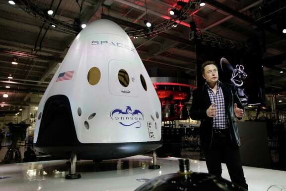 In this May 29, 2014 photo, Elon Musk, CEO and CTO of SpaceX, introduces the SpaceX Dragon V2 spaceship at the SpaceX headquarters in Hawthorne, Calif. On Tuesday, Sept. 16, 2014, NASA will announce which one or two private companies wins the right to transport astronauts to the International Space Station. The deal will end NASA's expensive reliance on Russian crew transport. The contenders include SpaceX, Sierra Nevada Corp., and Boeing.