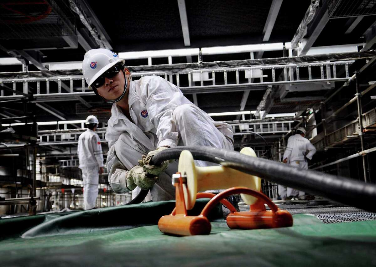 Workers lay cables on an oil rig under construction for China National Offshore Oil Corp. China is asserting a claim over nearly all the South China Sea.