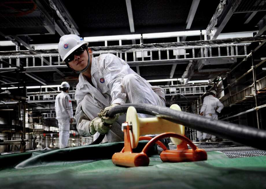 Workers lay cables on an oil rig under construction for China National Offshore Oil Corp. China is asserting a claim over nearly all the South China Sea. Photo: STR / CHINATOPIX