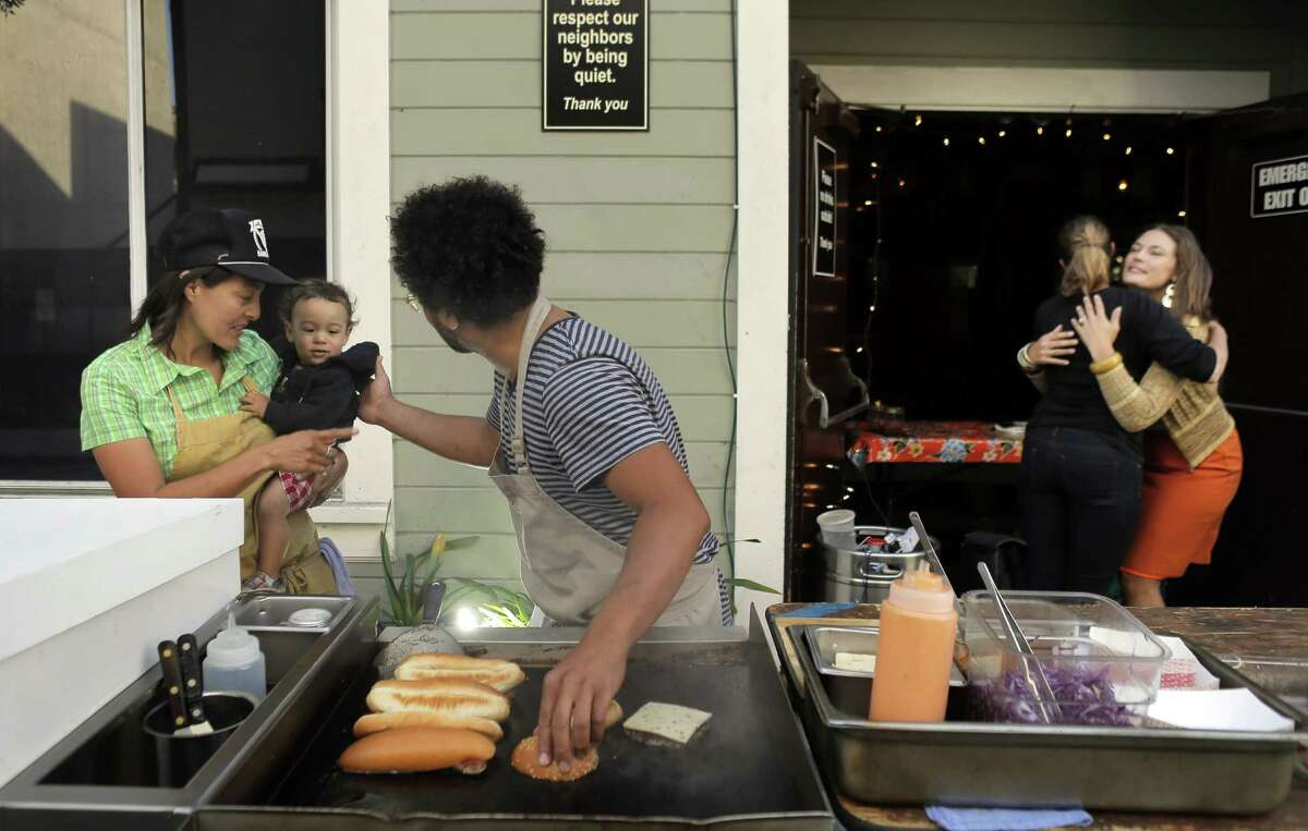 Chef Ravi Kapur (center) cooks with longtime sous chef Nana Guardia and her young son, Kaylon, at Paniolo Social Club, Kapur's pop-up at Bloodhound bar in S.F. The foods are inspired by his Hawaiian childhood.