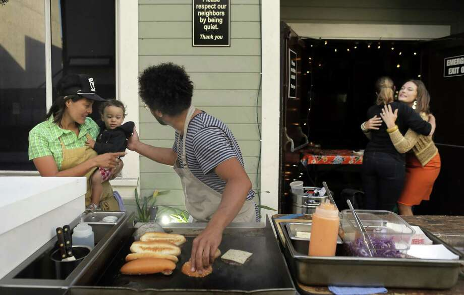Chef Ravi Kapur (center) cooks with longtime sous chef Nana Guardia and her young son, Kaylon, at Paniolo Social Club, Kapur's pop-up at Bloodhound bar in S.F. The foods are inspired by his Hawaiian childhood. Photo: Carlos Avila Gonzalez, Staff Photographer / The Chronicle / ONLINE_YES