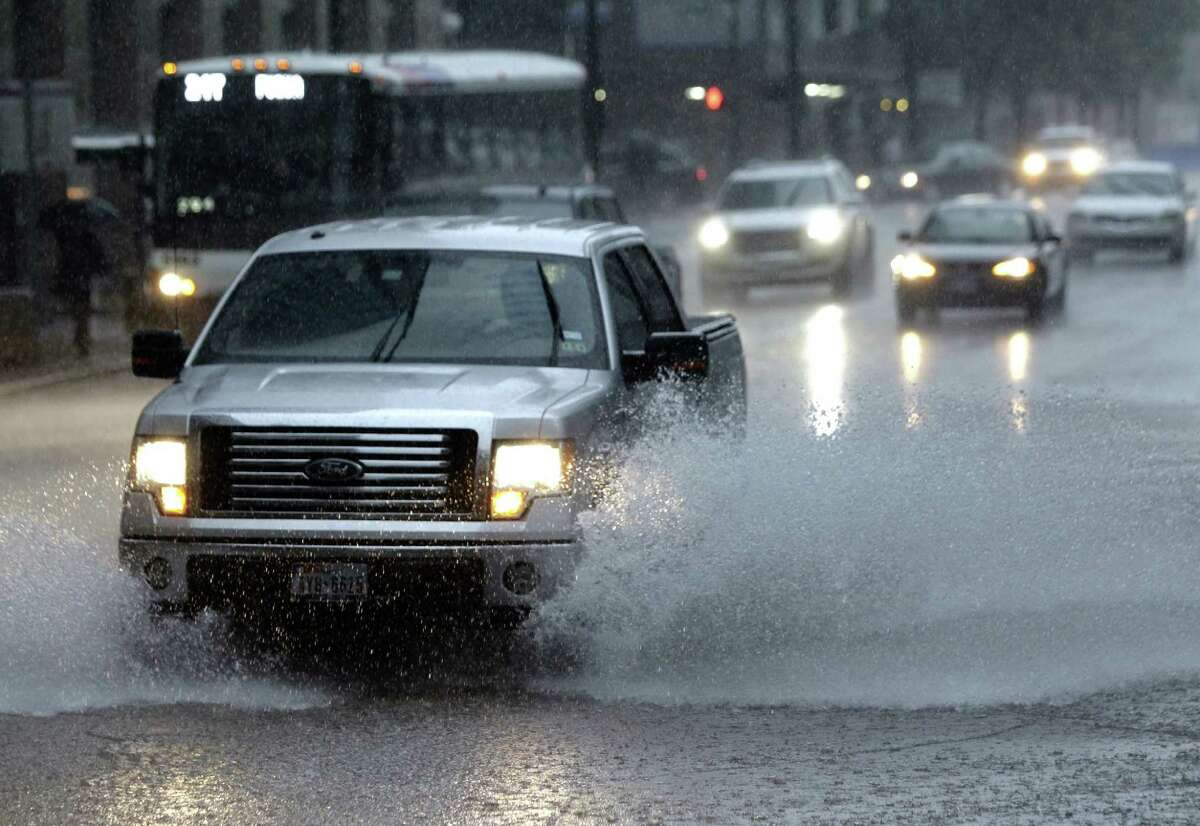 Vehicles pass through a storm in downtown Tuesday, Sept. 16, 2014.