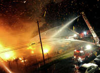 Firefighters battle a massive fire which erupted at an industrial site along Seaview Avenue in Bridgeport, Conn., on Thursday Sept. 11, 2014. Fire cews from Fairfield and Stratford responded with equipment and manpower to help battle the blaze.