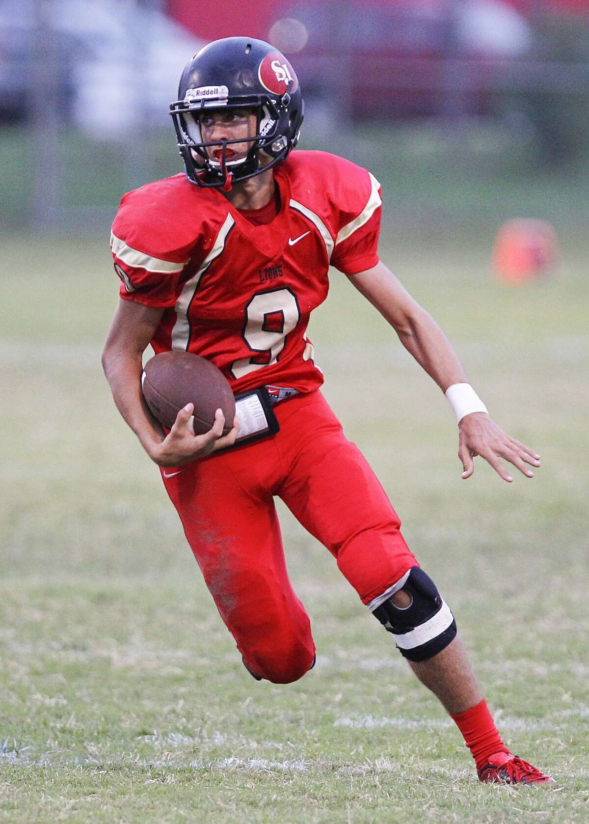 St. John XXIII quarterback Tristan Kuebler runs for the quarterback keep as the Lions faced off against Danbury in a non-district game at St. John XXIII College Prep in Katy on September 12, 2014.