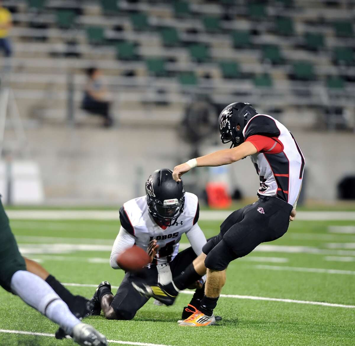 Langham Creek and Cy Falls football teams met at the Berry Center, 9-11-2014, for a 17-5A District contest. Langham Creek won the contest, 43-39. Right, Langham place kicker Joel Scarbrough (16) kicked an extra point as Paul Watson (14) holds the ball.