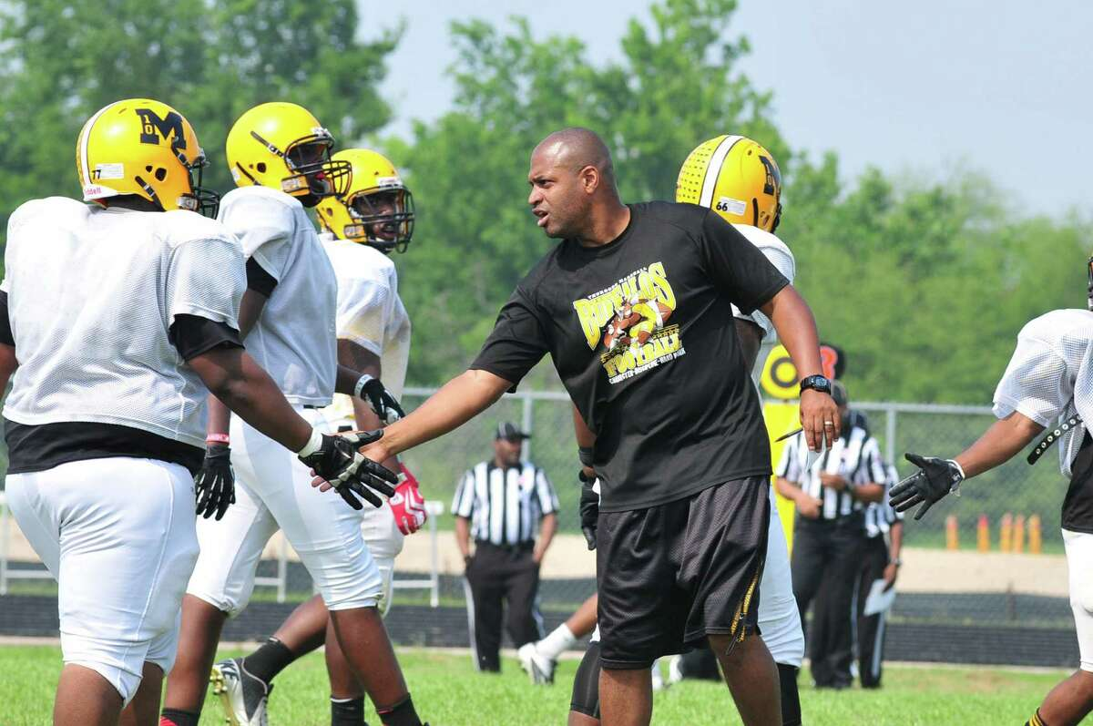 Fort Bend Marshall football head coach James Williams congratulates his offense as he leads his team in an inter-squad scrimmage Friday 5/17/13. Photo by Tony Bullard.