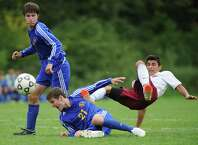 Newtown's Forrest Weatherby, left, watches as his teammate James Cochrane, center, gets tangled up with Bethel's Kyle Almeida in the 1-1 tie between Bethl and Newtown in the high school boys soccer game at Rourke Field in Bethel, Conn. Tuesday, Sept. 16, 2014.