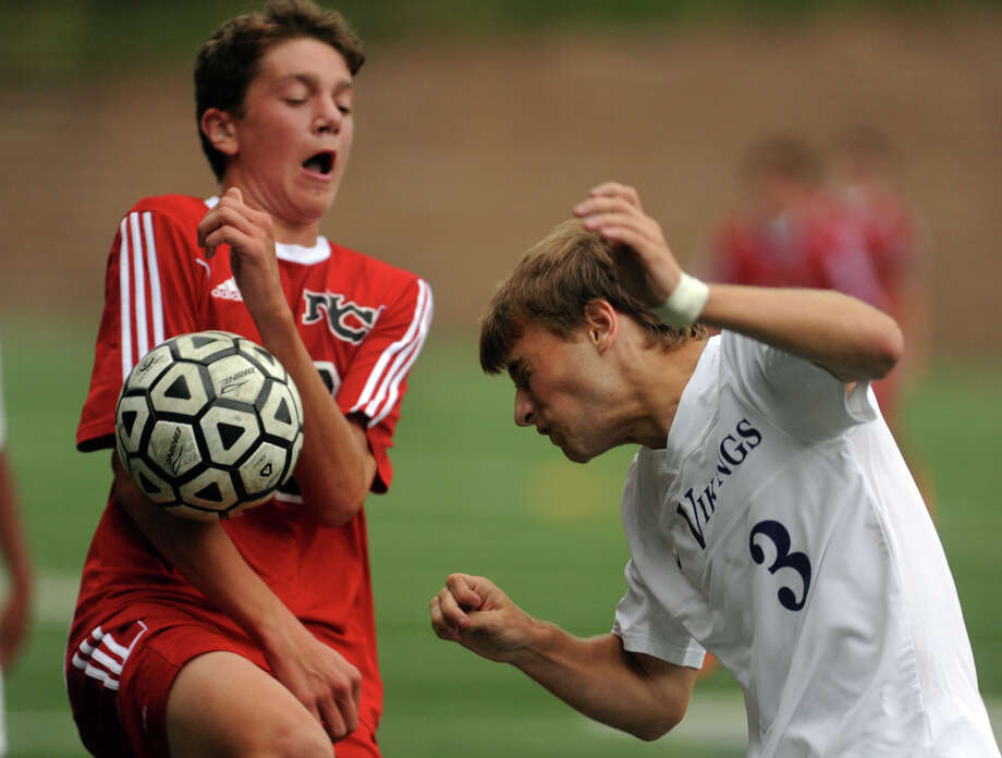 Westhill's Tomas Pinto-Leite, right, heads the ball as New Canaan's Brett Capone deflects it with his chest, during boys soccer action in Stamford,  Conn., on Tuesday Sept. 16, 2014. Photo: Christian Abraham / Connecticut Post