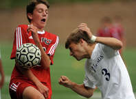 Westhill's Tomas Pinto-Leite, right, heads the ball as New Canaan's Brett Capone deflects it with his chest, during boys soccer action in Stamford,  Conn., on Tuesday Sept. 16, 2014.
