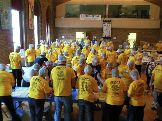 More than 130 volunteers from five local Lutheran congregations donned yellow T-shirts (and hair nets) on Sept. 7 and packed some 30,000 meals for distribution to area food pantries as part of ?God?s work, Our hands,? a day of service celebrated by Lutherans around the country. The action above is at First Lutheran Church in Albany with participants from there and four other congregations, St. John?s, St. Paul?s and Lutheran Church of the Holy, and Good Shepherd in Loudonville.