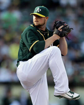 Oakland Athletics' Jon Lester works against the Los Angeles Angels in the first inning of a baseball game Saturday, Aug. 23, 2014, in Oakland, Calif. (AP Photo/Ben Margot)