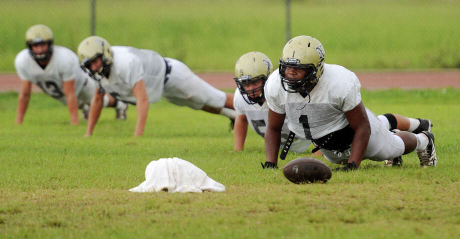 Leon Mayfield, left, and other Nederland players warm up for Tuesday's practice. The Nederland Bulldogs practiced in a light rain Tuesday afternoon. Photo taken Tuesday 9/16/14 Jake Daniels/@JakeD_in_SETX Photo: Jake Daniels / ©2014 The Beaumont Enterprise/Jake Daniels