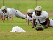Leon Mayfield, left, and other Nederland players warm up for Tuesday's practice. The Nederland Bulldogs practiced in a light rain Tuesday afternoon. Photo taken Tuesday 9/16/14 Jake Daniels/@JakeD_in_SETX