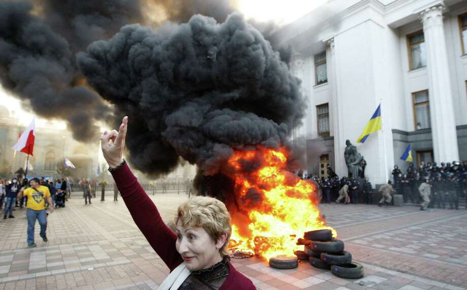 A woman salutes protesters who burned tires outside the Ukrainian Parliament in Kiev. Photo: Yuri Kirnichny / Getty Images / AFP