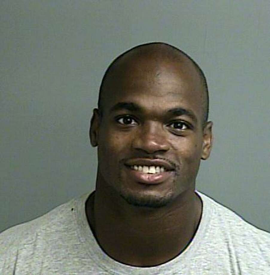 This photo provided by the Montgomery County sheriff's office shows the booking photo of Adrian Peterson.  Peterson was indicted in Texas for using a branch to spank one of his sons and the Minnesota Vikings promptly benched him for their game Sunday, Sept. 14, 2014 against the New England Patriots. Peterson turned himself in early Saturday at a jail in Montgomery County, near Houston, where he has a home. He was processed and released.  (AP Photo/Montgomery County sheriff's office) Photo: HOPD / Montgomery County sheriff's