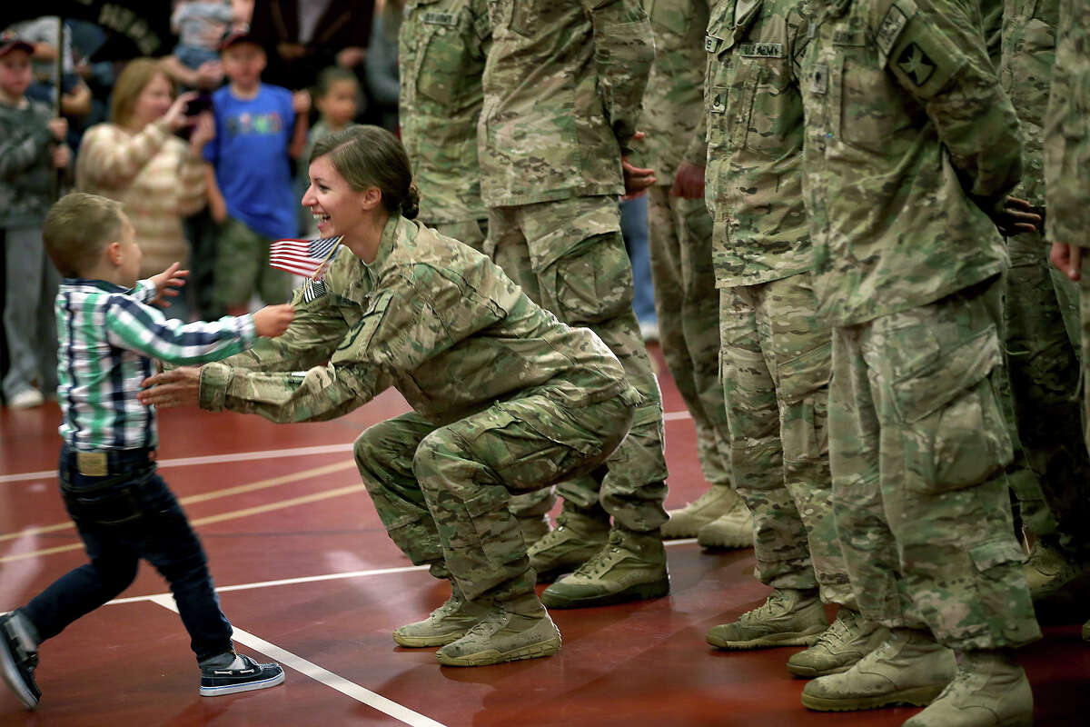 Cooper Waldvogel, 3, runs to hug his mother Kathryn Waldvogel after her return from Afghanistan at the Inver Grove Heights Training Center, Tuesday, Sept. 16, 2014 in Inver Grove Heights, Minn. More than 140 soldiers from the Minnesota National Guard's Chisholm-based 114th Transportation Company returned to Minnesota after a nine-month deployment to Afghanistan.
