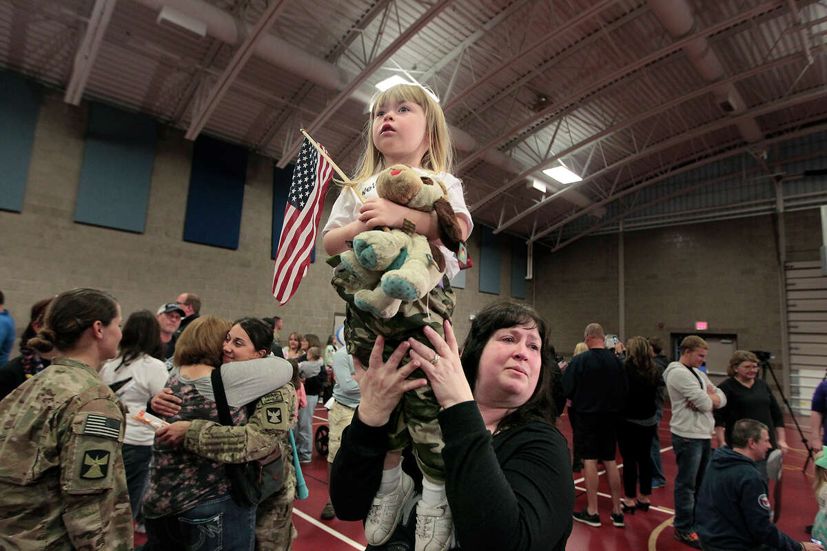 Robin Anderson holds up her granddaughter Kinlee Anderson, as she searches for her father Brady Anderson, who is returning home from Afghanistan at the Inver Grove Heights Training Center, Tuesday, Sept. 16, 2014 in Inver Grove Heights, Minn.